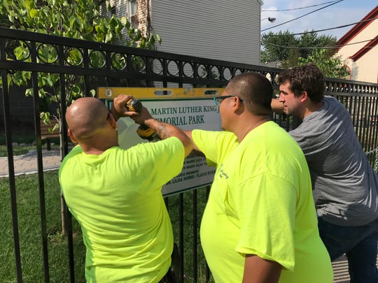 Paterson DPW workers Carlos Piereschi (R) and Gerber Hernandez hanging a sign with Jack Sigillito of Paterson Habitat for Humanity.