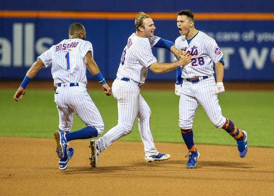Aug 21, 2019; New York City, NY, USA; New York Mets left fielder J.D. Davis (28) celebrates with first baseman Pete Alonzo (20) and shortstop Amed Rosario (1) after hitting a game winning RBI single in the tenth inning to defeat the Cleveland Indians at Citi Field. Mandatory Credit: Wendell Cruz-USA TODAY Sports