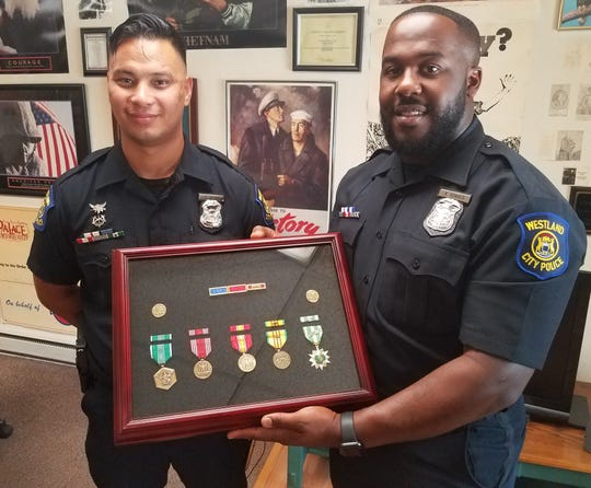 From left to right, Westland community policing Officers Chaim Kozak and Rodney Donald show off the shadow box filled with medals that would replace ones stolen from a local veteran, Vince Berna, the founder of Veteran's Haven in Wayne.