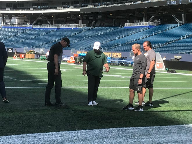 Green Bay Packers general manager Brian Gutekunst (in white hat) looks over a part of the turf at IG Field in Winnipeg on Thursday afternoon.