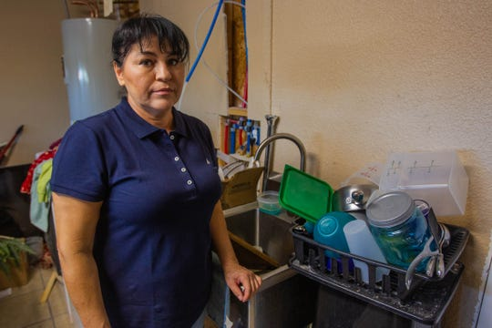 Filomena Parra stands by the sink her boyfriend built her in the garage after her kitchen remodel was left unfinished, which has left her without a kitchen sink or stove for 6 months.