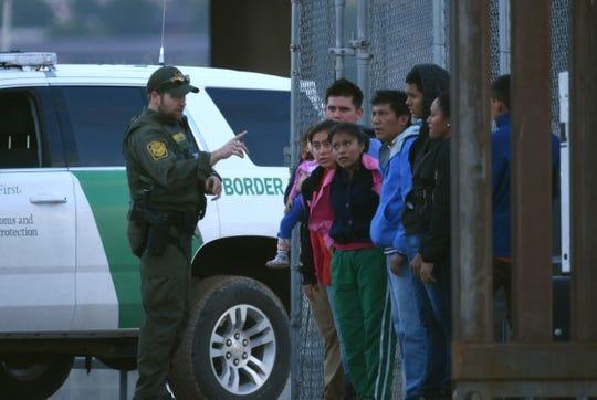 Un agente de la patrulla fronteriza estadounidense habla a un grupo de jóvenes migrantes centroamericanos tras ser detenidos en los margenes del Rio Bravo, en la fronteriza Ciudad Juárez.
