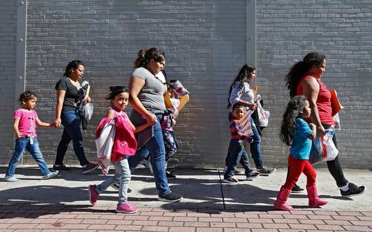 Familias de migrantes reaccionan tras ser procesadas en la Estación Central de Autobuses de McAllen, Texas.