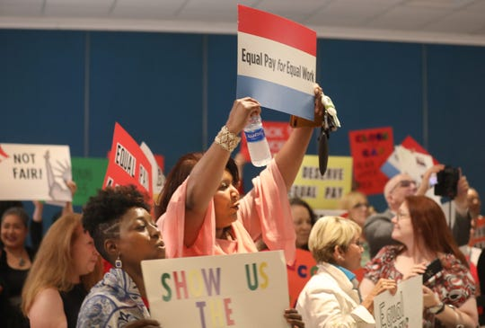 Supporters for equal pay for women hold up signs at a rally on August 22, 2019.