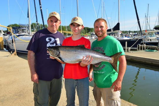 Austin Hoitt holds his 18-pound king salmon, which won the Scouting division at 26th annual Casting for Character Sports Fishing Tournament. His dad, BSA executive Stephen Hoitt, is left and Hammerhead Charter captain Jim Piano.