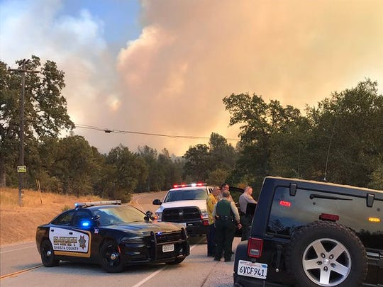 Authorities gather around a road closure due to the Mountain Fire.