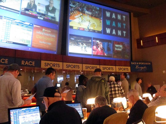 FILE - In this March 21, 2019, file photo, gamblers line up to place bets on the NCAA men's college basketball tournament at the Borgata casino in Atlantic City N.J. This is the first March Madness tournament since legal gambling expanded last year in the U.S.  The spread of legalized sports betting is largely following regional boundaries. Lawmakers across the Northeast and upper Midwest have generally approved it or are still considering doing so this year. But in the Deep South and far West, fewer states are rushing in a year after the US Supreme Court cleared the way for legal sports betting nationally.