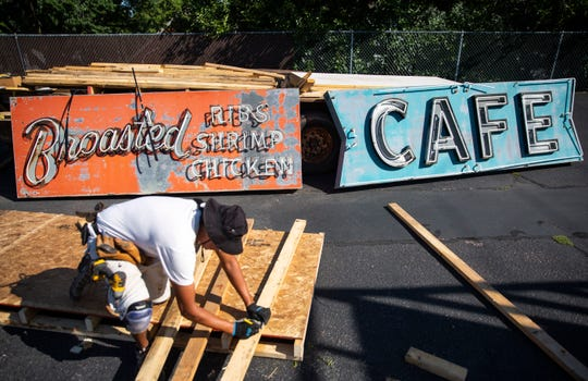 Jeff Noisy Hawk builds crates to safely transport the iconic Bob's Cafe sign on West 12th Street on Thursday, Aug. 22.