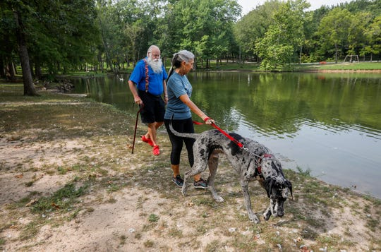 Jim and Denise Bethurem walk their dog Buddy near Dunnegan Lake in Bolivar on Wednesday, Aug. 21, 2019. Dunnegan Lake is the only body of water in southwest Missouri where blue-green algae has been reported.