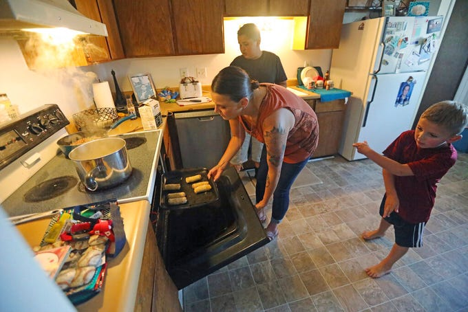 Misty Dotson prepares dinner for her son's at their home Tuesday, Aug. 20, 2019, in Murray, Utah. Dotson is a 33-year-old single mother of two boys, ages 12 and 6, who goes to Planned Parenthood for care through the Title X program. Dotson is among the 39,000 people received treatment from Planned Parenthood of Utah in 2018 under a federal family planning program called Title X. The organization this week announced it is pulling out program rather than abide by a new Trump administration rule prohibiting clinics from referring women for abortions. (AP Photo/Rick Bowmer)