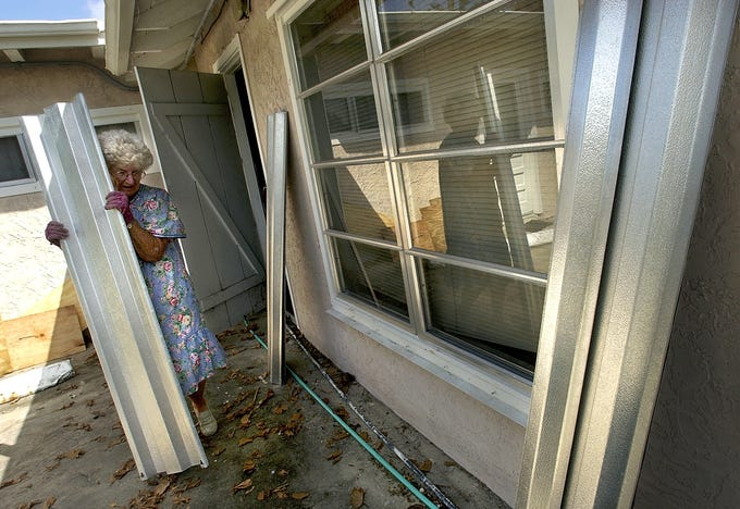 Eileen Eiler, 80, of Jensen Beach put up her hurricane shutters Sept. 23, 2004, for the second time in a month as Hurricane Jeanne threatened to make landfall on the Treasure Coast. Eiler sustained some damage from Hurricane Frances and decided not to wait to the last minute to board up for Jeanne.