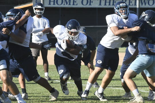 The Redwood High School football team practices on Aug. 19, 2019 in Visalia.