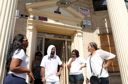 Community activist Lorraine Lopez, right, speaks with advocate Mathew Medina and displaced residents Rosa Reyes, left, Grace Gray and Millissa Garcia outside 149 N. Broadway in Yonkers Aug. 22, 2019. A fire on August 11 displaced nearly 90 residents, including 38 children, and many of them still need help finding a home.