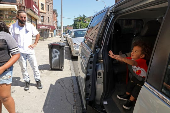 Mathew Medina, 32, is overcome with emotion as his 1-year-old son Xavier Medina reaches out from the family van Aug. 22, 2019 outside 149 N. Broadway in Yonkers. Medina is advocating for his family who lives in the building that a fire on August 11 displaced nearly 90 residents, including 38 children. Many of them still need help finding a home.