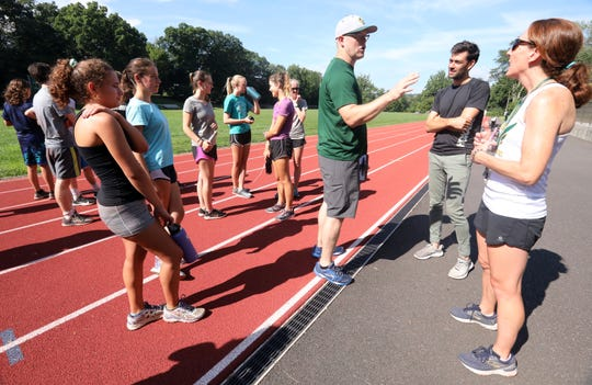 Hastings cross-country coach Molly Guilfoyle, right, professional runner Kyle Merber and athletic director Jesse Merchant chat after Merber met with cross-country runners at Reynolds Field Aug. 22, 2019 in Hastings.
