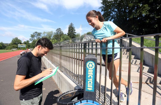 Hastings resident Kyle Merber, a professional runner with the NJ-NY HOKA club, signs his autograph for junior Kaylee Oppenheimer after meeting with the cross-country team to answer questions and share advice on running at Reynolds Field Aug. 22, 2019 in Hastings.