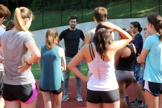 Hastings resident Kyle Merber, a professional runner with the NJ-NY HOKA club, gives Hastings High School cross-country runners advice at Reynolds Field Aug. 22, 2019 in Hastings.