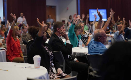Members of the audience attending a roundtable discussion put together by Sen. Chris Coons with special guest Dir. James Carroll, of the National Office of Drug Control Policy, raise their hands when ask if anyone knows a person struggling with addiction.