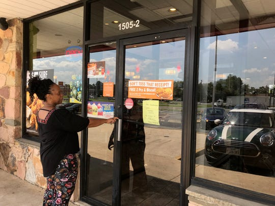 Maureen Ogilvie stops outside a local Popeyes restaurant to read the sign that the popular chicken sandwich is not in stock.