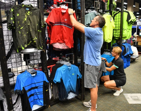 Darren Poore and Paulien Van Etten help organize apparel for Sun & Ski Sports at the Hotter'N Hell Hundred Consumer Show Thursday afternoon at the Ray Clymer Exhibit Hall.