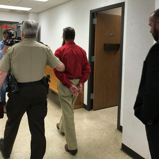 A Wichita County law-enforcement officer leads Jonathan Darrell Woody from the 30th District Courtroom Thursday to Wichita County Jail.