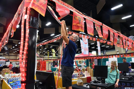 Blaise Mikulewicz of Richardson Bike Mart adds rope lights to the company's booth space at the Hotter'N Hell Hundred Consumer Show Thursday at the Ray Clymer Exhibit Hall.