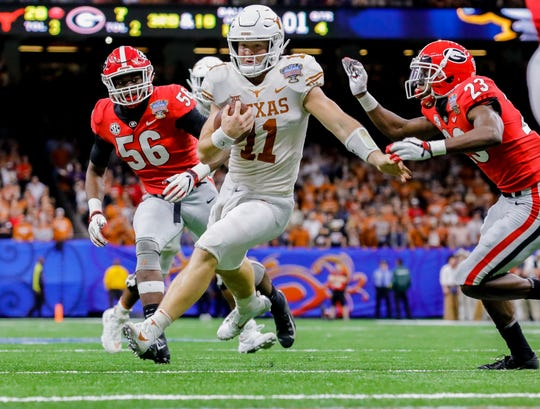 Texas quarterback Sam Ehlinger tries to avoid Georgia defenders while running during the 2019 Sugar Bowl.