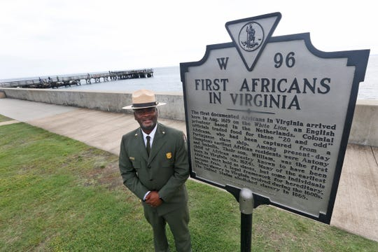 Terry E. Brown, Superintendent of the Fort Monroe National Monument poses next to a historical marker that signifies the spot of the first landing of Africans in America 400 years ago at Fort Monroe in Hampton, Va., Thursday, Aug. 15, 2019.