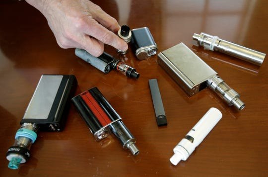 Marshfield High School Principal Robert Keuther displays vaping devices that were confiscated from students in such places as restrooms or hallways at the school in Marshfield, Mass., on April 10, 2018.