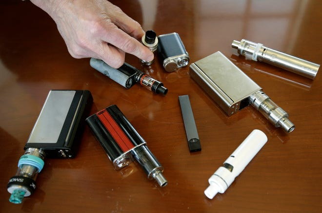 Marshfield (Mass.) High School Principal Robert Keuther displays vaping devices that were confiscated from students in  restrooms or hallways at the school in this April 2018 file photo. Officials on Wednesday, Aug. 21, 2019, said the Food and Drug Administration has joined the Centers for Disease Control and Prevention and a number of states in the investigation of breathing illnesses among people who vape. Health officials are now looking into more than 150 possible cases in 16 states.
