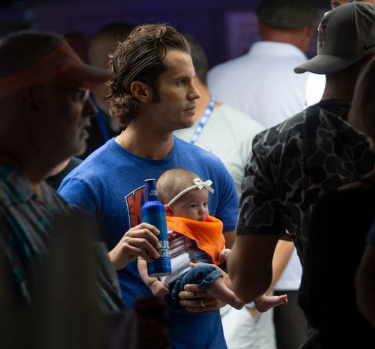 Steve Fortunato, 29, of Belmar, drinks a beer while he attends the event with his baby and wife. People attend the WFAN's Mike Francesa Summer Send-Off show at Bar Anticipation in Lake Como, NJ on August 23, 2019.