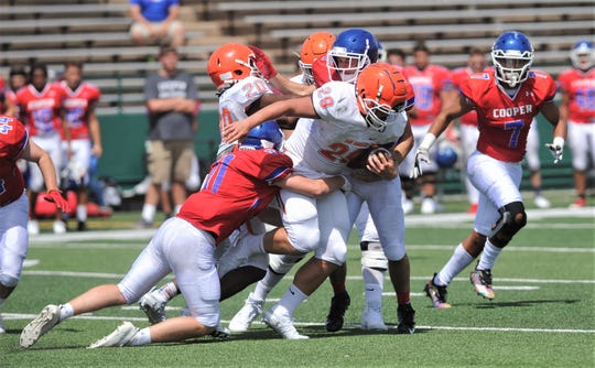 The Cooper defense tries to bring down a San Angelo Central runner during a scrimmage Friday, Aug. 23, 2019, at Shotwell Stadium.