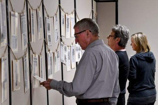 Jerry Cannon, Patty Payne and Crystal Latham look over a display of laminated newspaper clippings about Haskell Memorial Hospital over the years. The hospital celebrated 80 years Thursday with an open house.