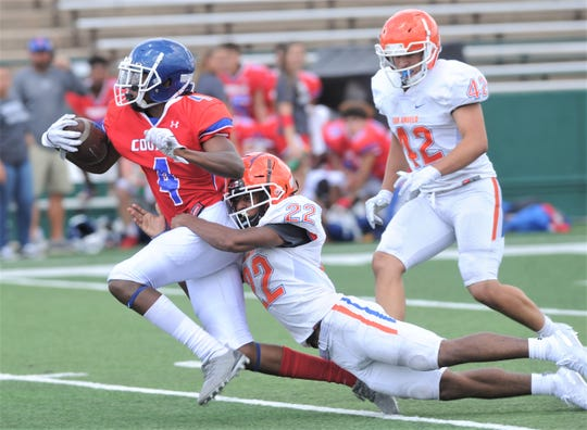 A San Angelo Central defender tries to bring down Cooper receiver Nyjil Williams after a long pass play during a scrimmage Friday at Shotwell Stadium.