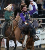 Bareback rider Tilden Hooper, of Carthage, Texas, loses his hat as he rides a horse named Bonanza during the Kitsap County Stampede on Thursday.