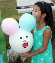 Phoebe Dominguiano, 5, takes a giant bite out of her bunny rabbit cotton candy character during the Kitsap County Fair last month. The fair saw a big bump in attendance this year that organizers are attributing to free admission.
