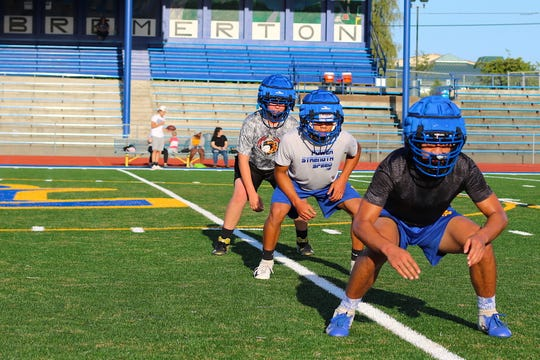 Bremerton senior Kaipo Retome (right) leads the team's linebackers through a drill at practice on Aug. 22, 2019.