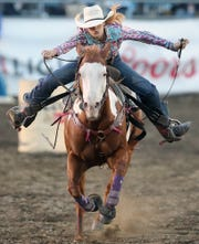 Barrel racer Jackie Ganter, of Abilene, Texas, heads for the finish line during the Kitsap County Stampede on Thursday.