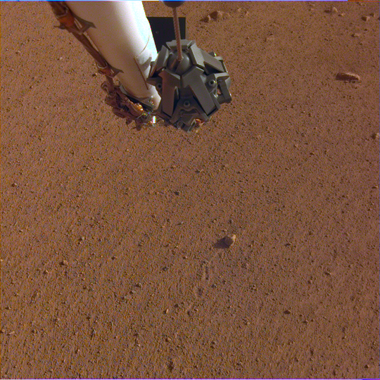 "The rock in the center of this image was tossed about 3 feet (1 meter) by NASA's InSight spacecraft as it touched down on Mars on November 26, 2018. The rock, which is a little bigger than a golf ball, was later nicknamed ""Rolling Stones Rock"" in honor of The Rolling Stones."