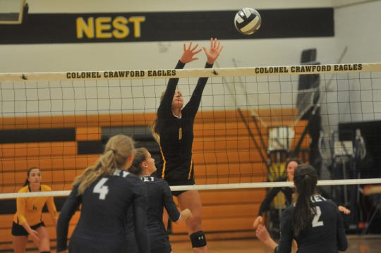 Colonel Crawford's Keirsten O'Rourke jumps up to block a ball at the net.