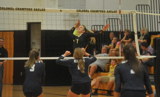 Colonel Crawford's Jenna Maddy jumps up and readies herself to hit a ball at the net.