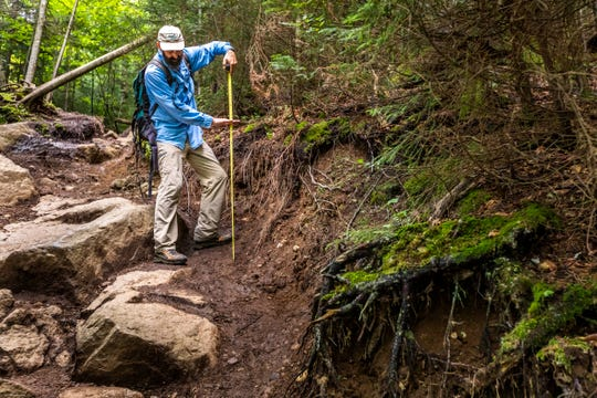 William Janeway, executive director of the nonprofit Adirondack Council, measures trail erosion on Ampersand Mountain in the High Peaks region of the Adirondack Park in August 2018.