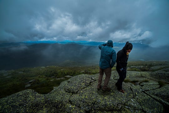 David LeMay and Monika Baumgart, traveling trainers with the Leave No Trace Center for Outdoor Ethics, look out from Algonquin Peak in the Adirondack Park on Saturday, August 10, 2019. LeMay and Baumgart were helping summit stewards educate hikers in leave-no-trace practices while in the backcountry.