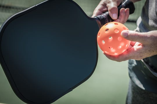A player holds a pickleball and racket in this USA Today file photo.