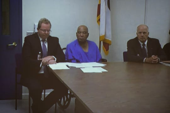 Samuel Little, center, pleads guilty to two murders while sitting next to his defense attorney, Tim McKenna, left, and Hamilton County Assistant Prosecutor,  Mark Piepmeier, right, from a video feed from a state prison in California to the Hamilton County Courthouse in Cincinnati. Little is currently serving multiple life sentences for murder in California and has claimed to have killed 93 people.