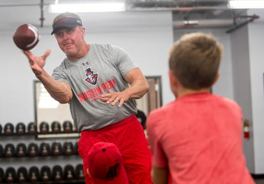Austin Peay coach Mark Hudspeth and son Major, 9, toss the football Thursday after practice at Fortera Stadium.
