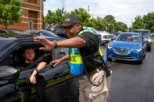 Officer Derrick Oliver helps point new people arriving to parking on the first day of freshman move-in at Austin Peay State University in Clarksville, Tenn., on Thursday, Aug. 22, 2019.