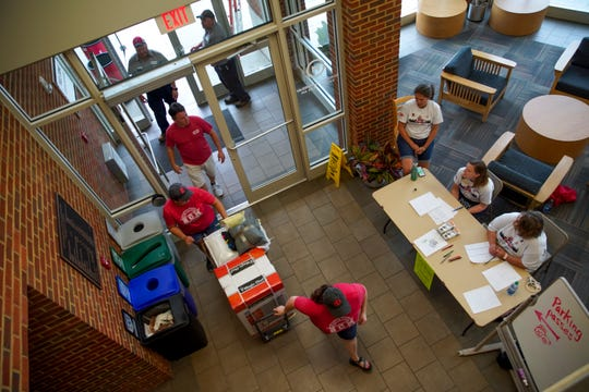 Students and family walk into dorms to register and get their keys on the first day of freshman move-in at Austin Peay State University in Clarksville, Tenn., on Thursday, Aug. 22, 2019.