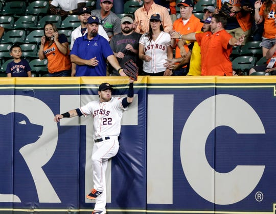 Josh Reddick catches a deep fly ball at the wall in the ninth inning to secure a 6-3 win over the Tigers.