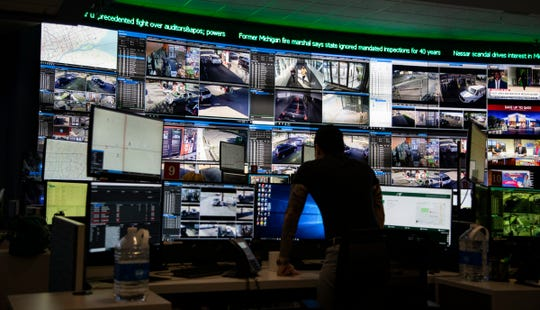 A crime analyst looks over several different surveillance cameras positioned around Detroit in the police department's crime intelligence center.